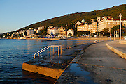 View of Opatija in early morning light, with concrete ocean-front and steps in foreground. Opatija, Croatia