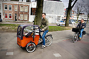 In Utrecht fietst een man met een kind en kinderfiets in de bakfiets.<br /> <br /> In Utrecht a man cycles with a child and a child's bike in a cargobike.