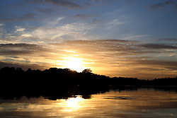 The sun sets on a autumn day at Virginia Water in Surrey.