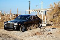 Rolls Royce parked next to broken chair in abandoned village