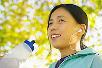 Young female runner with water bottle and MP3 player.