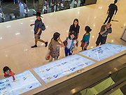 "27 MARCH 2015 - BANGKOK, THAILAND: Shoppers at the information board in ""EmQuartier,"" a new mall in Bangkok. ""EmQuartier"" is across Sukhumvit Rd from Emporium. Both malls have the same corporate owner, The Mall Group, which reportedly spent 20Billion Thai Baht (about $600 million US) on the new mall and renovating the existing Emporium. EmQuartier and Emporium have about 450,000 square meters of retail, several hotels, numerous restaurants, movie theaters and the largest man made waterfall in Southeast Asia. EmQuartier celebrated its grand opening Friday, March 27.    PHOTO BY JACK KURTZ"