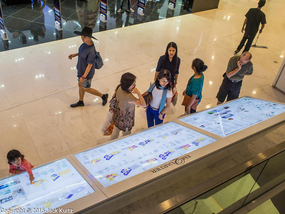 """27 MARCH 2015 - BANGKOK, THAILAND: Shoppers at the information board in """"EmQuartier,"""" a new mall in Bangkok. """"EmQuartier"""" is across Sukhumvit Rd from Emporium. Both malls have the same corporate owner, The Mall Group, which reportedly spent 20Billion Thai Baht (about $600 million US) on the new mall and renovating the existing Emporium. EmQuartier and Emporium have about 450,000 square meters of retail, several hotels, numerous restaurants, movie theaters and the largest man made waterfall in Southeast Asia. EmQuartier celebrated its grand opening Friday, March 27.    PHOTO BY JACK KURTZ"""