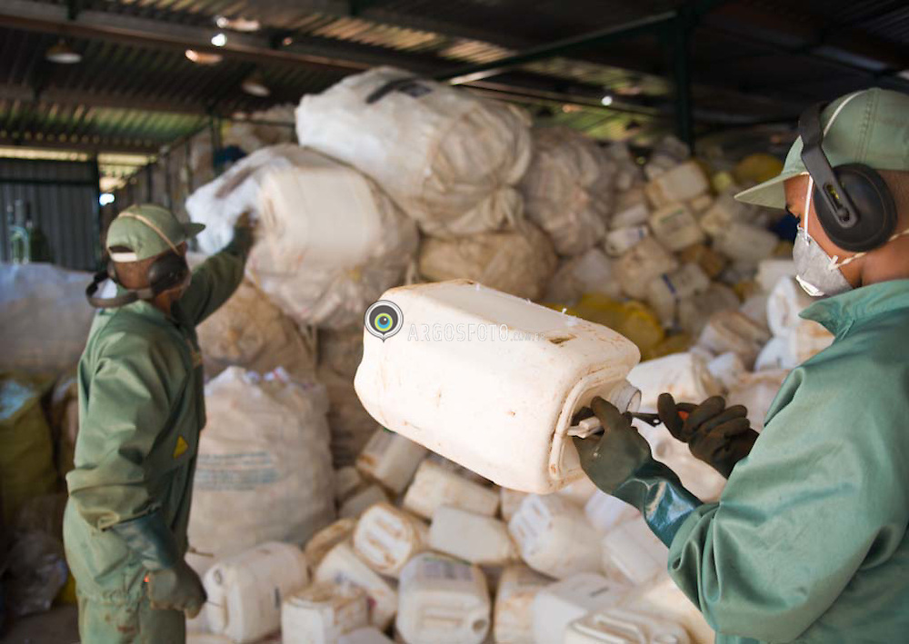 Empty agrochemicals containers. Worker sorting containers out by type (PET, COEX, HDPE, Metallic, cardboard) to be  recycled in Brazil / Embalagens de agrotoxicos sendo selecionadas e preparadas para reciclagem.