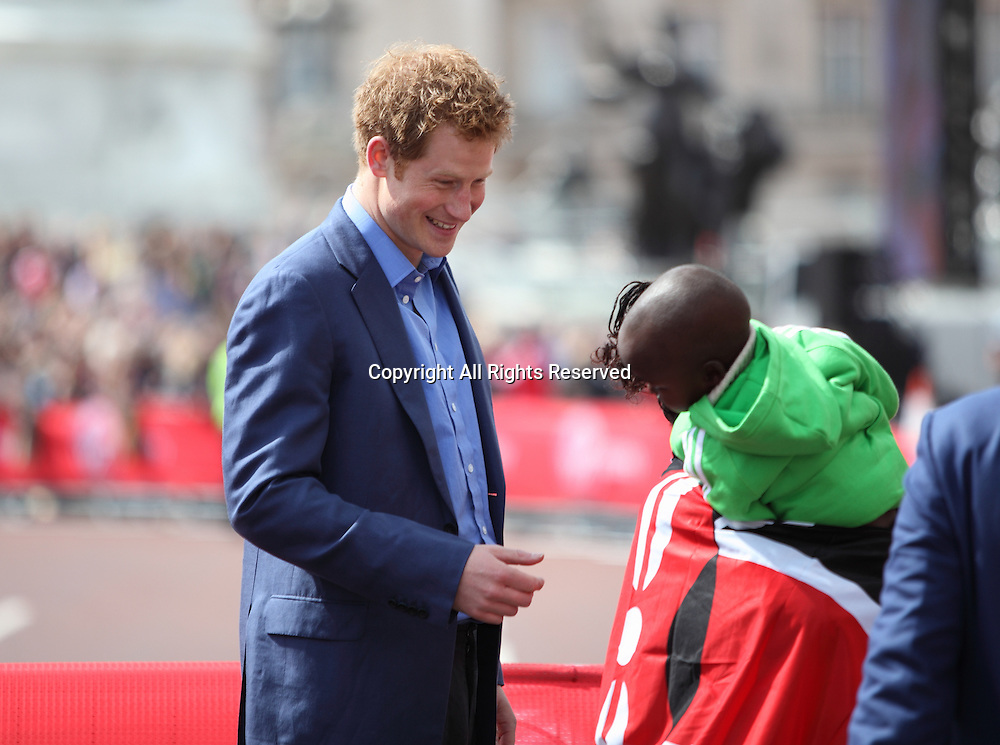 22.04.2012 London, England. Prince Harry smiles and shares a joke witht the womens winner Mary Keitany (Kenya)and her young baby on the Mall, London.