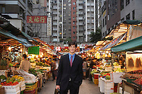 Portrait of young business man at street market