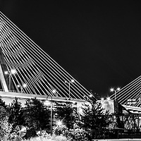 Zakim Bunker Hill Bridge at night black and white Boston panoramic photo. The Leonard P. Zakim Bunker Hill Memorial Bridge is a cable bridge that spans the Charles River in Boston, Massachusetts in the Eastern United States or America. Panorama photo ratio is 1:3. Copyright ⓒ Paul Velgos with All Rights Reserved.