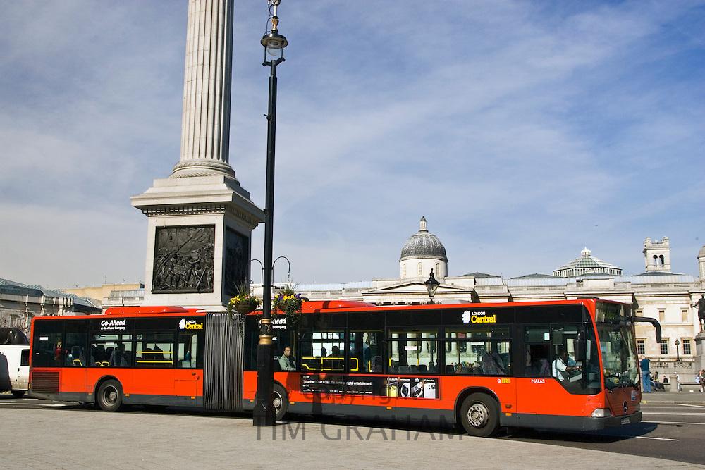 Public transport single-decker bendy bus travelling in Trafalgar Square, London city centre, England, United Kingdom