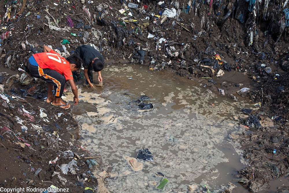 Boys wash their hands and feet in a puddle in Kampung Bolero, Dayeuhkolot district, Bandung regency, Indonesia. Sludge and trash dredged from the riverbed is now piled up on the riverbank. ..The Citarum river, which runs about 270 kilometers through the province of West Java, is considered to be among the world's dirtiest. Over the last twenty years, the river has been severely polluted by toxic industrial waste, trash and raw sewage. The Citarum is one of the main sources of freshwater for West Java and supplies about 80% of water for Indonesia's capital Jakarta.