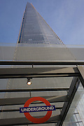 A London Underground sign beneath the tall architecture of the Shard at London Bridge.