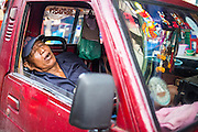 "26 SEPTEMBER 2012 - BANGKOK, THAILAND:  A truck driver sleeps in the cab of his truck in Khlong Toey Market in Bangkok. Khlong Toey (also called Khlong Toei) Market is one of the largest ""wet markets"" in Thailand. The market is located in the midst of one of Bangkok's largest slum areas and close to the city's original deep water port. Thousands of people live in the neighboring slum area. Thousands more shop in the sprawling market for fresh fruits and vegetables as well meat, fish and poultry.    PHOTO BY JACK KURTZ"
