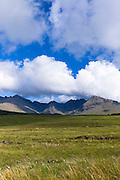 Puffy white cumulus clouds over iconic Cuillin mountain range on Isle of Skye in the Highlands and Islands of Scotland