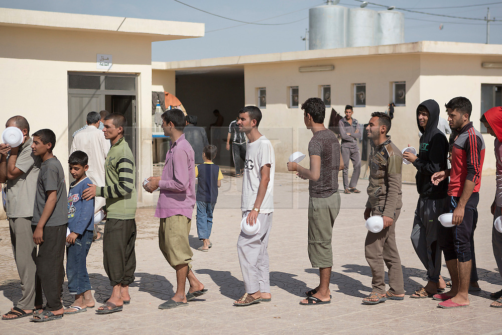Licensed to London News Pictures. 20/10/2016. Iraqi men, some of whom have recently fled areas where the ongoing operation to liberate Mosul is taking place, queue for food in the courtyard of a mosque in Dibaga refugee camp near Makhmur, Iraq.<br /> <br /> The crowded Dibaga camp, housing around 28,000 Sunni Arab refugees, is the main gathering point for new IDPs now fleeing areas where ISIS have been pushed out or are in conflict with the Iraqi Army. Photo credit: Matt Cetti-Roberts/LNP