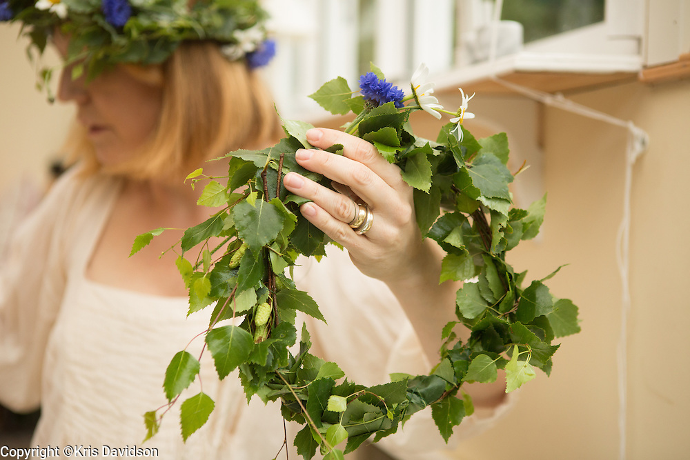 Woman prepares a Midsommar wreath on Öland, a Swedish island in the Baltic Sea. The longest day of the year is a beloved holiday in Sweden; the cities are empty as the locals take to the countryside for a day of dancing and singing with family and friends.