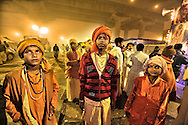 Three young pilgrims in Kumbh Mela going out from a tent after the sermon.