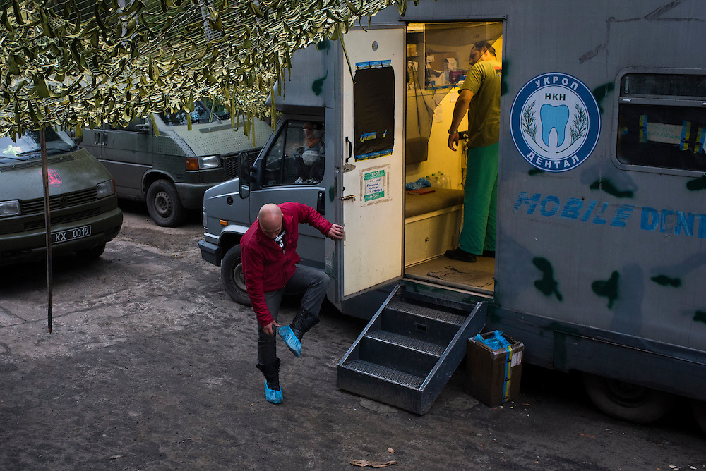 Ukrop Dental founder Igor Yaschenko removes covers from his shoes outside one of the program's mobile clinics on September 21, 2016 in Avdiivka, Ukraine.
