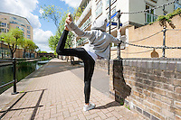Full length rear view of fit woman performing stretching exercise on sidewalk