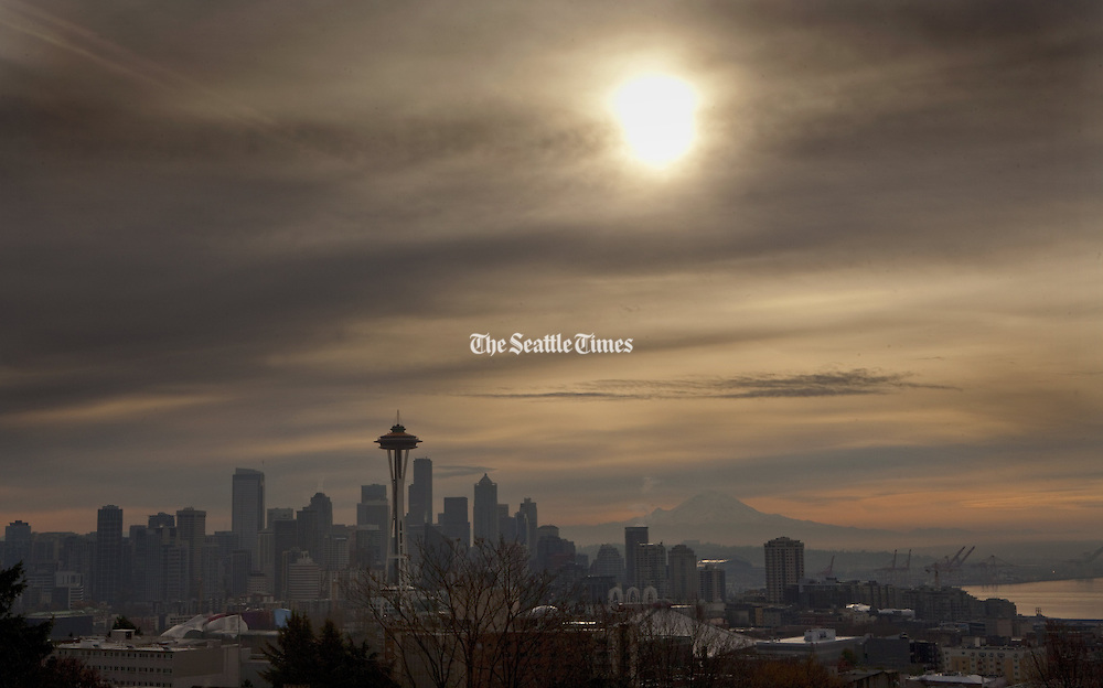Hazy skies hang above Seattle in the morning as Mt. Rainier looms in the background.<br /> Ellen M. Banner / The Seattle Times
