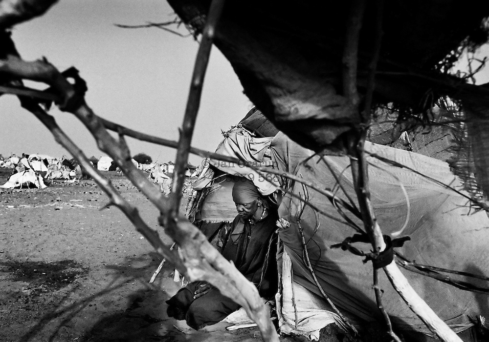 A newly-arrived refugee sits in her new tent. Not all of the arriving refugees are lucky enough to get a shelter but those who do often move into ones vacated by others.<br /> <br /> Kalma Camp, South Sudan - April 2005.
