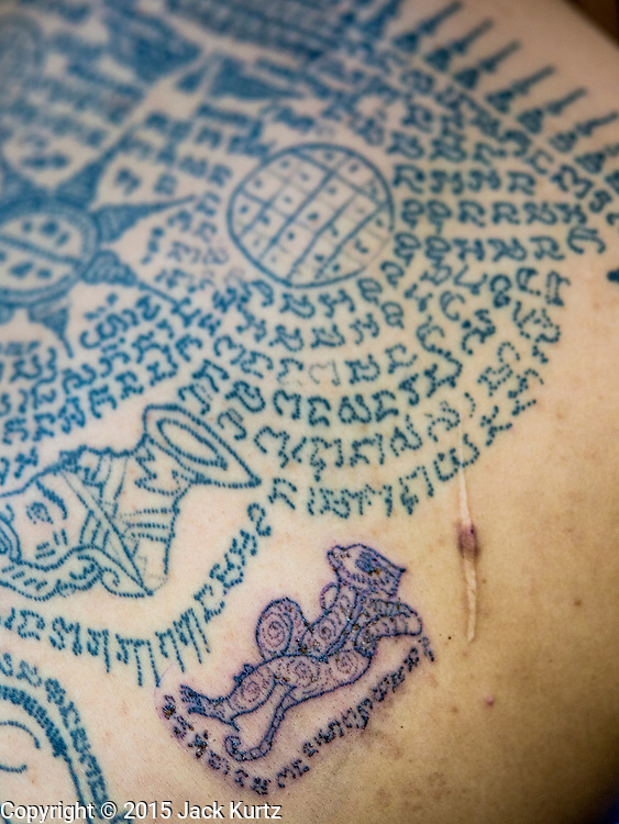 """07 MARCH 2015 - NAKHON CHAI SI, NAKHON PATHOM, THAILAND: Detail photo of Sak Yant tattoos on a man's back at the Wat Bang Phra tattoo festival. Wat Bang Phra is the best known """"Sak Yant"""" tattoo temple in Thailand. It's located in Nakhon Pathom province, about 40 miles from Bangkok. The tattoos are given with hollow stainless steel needles and are thought to possess magical powers of protection. The tattoos, which are given by Buddhist monks, are popular with soldiers, policeman and gangsters, people who generally live in harm's way. The tattoo must be activated to remain powerful and the annual Wai Khru Ceremony (tattoo festival) at the temple draws thousands of devotees who come to the temple to activate or renew the tattoos. People go into trance like states and then assume the personality of their tattoo, so people with tiger tattoos assume the personality of a tiger, people with monkey tattoos take on the personality of a monkey and so on. In recent years the tattoo festival has become popular with tourists who make the trip to Nakorn Pathom province to see a side of """"exotic"""" Thailand.   PHOTO BY JACK KURTZ"""