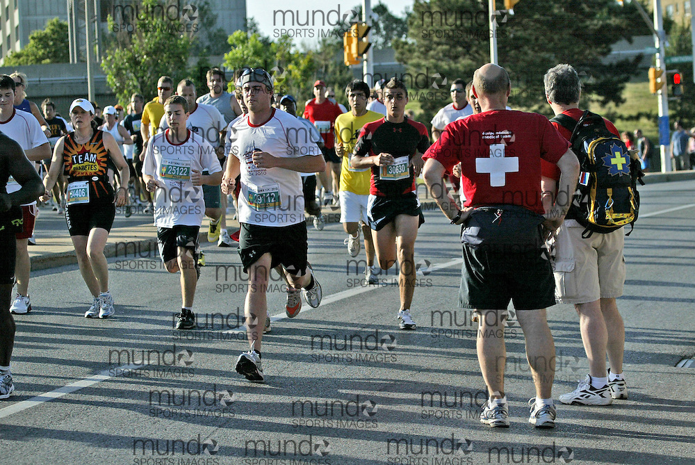 (Ottawa, ON --- May 29, 2010) First aid volunteer workers watch the runners pass in the 10km race during the Ottawa Race Weekend. Photograph copyright Sean Burges / Mundo Sport Images