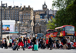 Pedestrians crossing street at Princes Street with Old Town Edinburgh to rear, Scotland, UK
