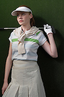Woman in visor holding golf club behind shoulders portrait