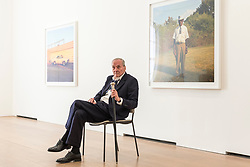 "© Licensed to London News Pictures. 10/04/2019. LONDON, UK.  American photographer William Eggleston poses in front of works from his new exhibition ""2¼"" at the David Zwirner gallery in Mayfair.  The show comprises a series of square-format colour photographs taken around 1977 throughout California and the American South and will run April 12 to June 1, 2019. Photo credit: Stephen Chung/LNP"