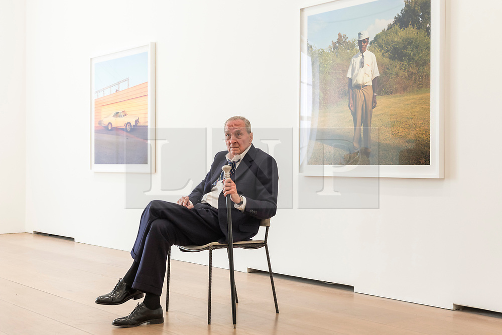 """© Licensed to London News Pictures. 10/04/2019. LONDON, UK.  American photographer William Eggleston poses in front of works from his new exhibition """"2¼"""" at the David Zwirner gallery in Mayfair.  The show comprises a series of square-format colour photographs taken around 1977 throughout California and the American South and will run April 12 to June 1, 2019. Photo credit: Stephen Chung/LNP"""