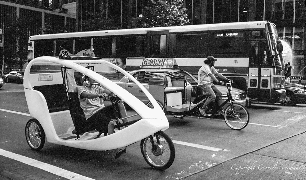Pedicabs. a taxi and a bus on Sixth Avenue