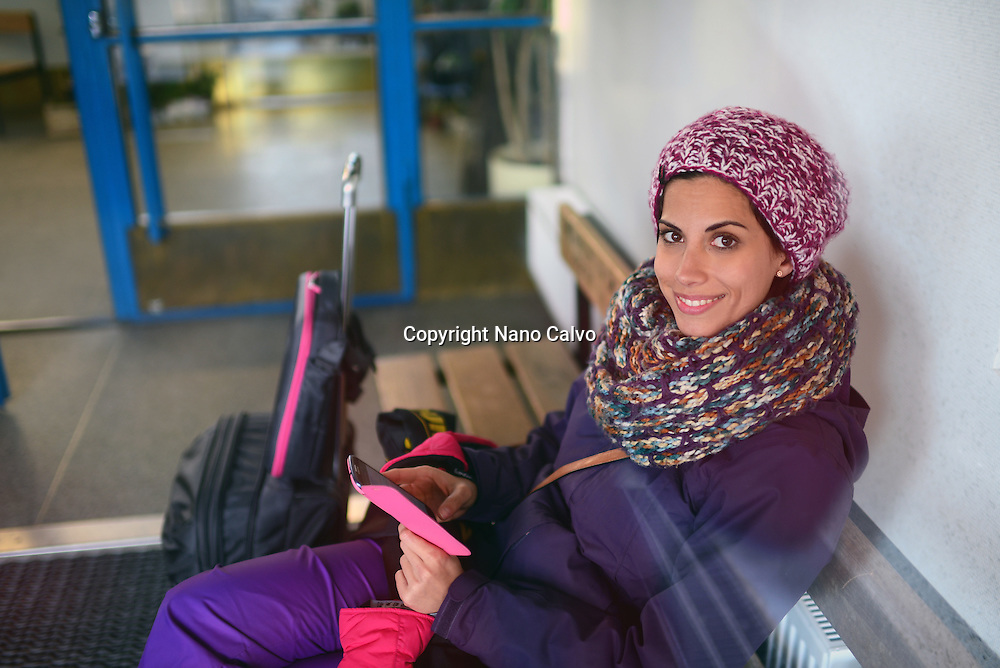 Young woman using mobile phone while waiting for the bus in Kemi Station, Lapland