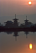 Pagodas of the Hosso Buddhist Yakushiji Temple point to the sun rising over Nara, the city that became Japan's first permanent capital in A.D. 710. The three-storied pagodas were built with mokoshi, inter-story pent roofs.