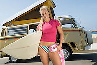 Young woman holding surfboard with camper van