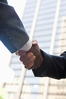 Close-up of businessmen handshake, outdoors