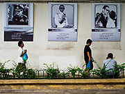 19 JULY 2017 - BANGKOK, THAILAND:    People walk past portraits of Bhumibol Adulyadej, the Late King of Thailand. The portraits are on a wall at Thammasat University. The King, also known as Rama IX, was the ninth of the King of the Chakri Dynasty and died after a long illness on October 13, 2016. He will be cremated on October 26, 2017.            PHOTO BY JACK KURTZ