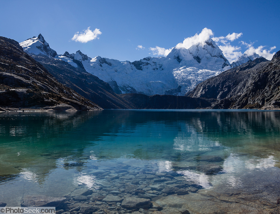 Nevado Santa Cruz Norte (5829 m or 19,120 ft) reflects in Lake Cullicocha (4628 m or 15,174 ft) in the morning. This was day 9 of 10 days trekking around Alpamayo in Huascaran National Park (UNESCO World Heritage Site), Cordillera Blanca, Andes Mountains, Peru, South America. Published in Wilderness Travel 2016 Catalog of Adventures.