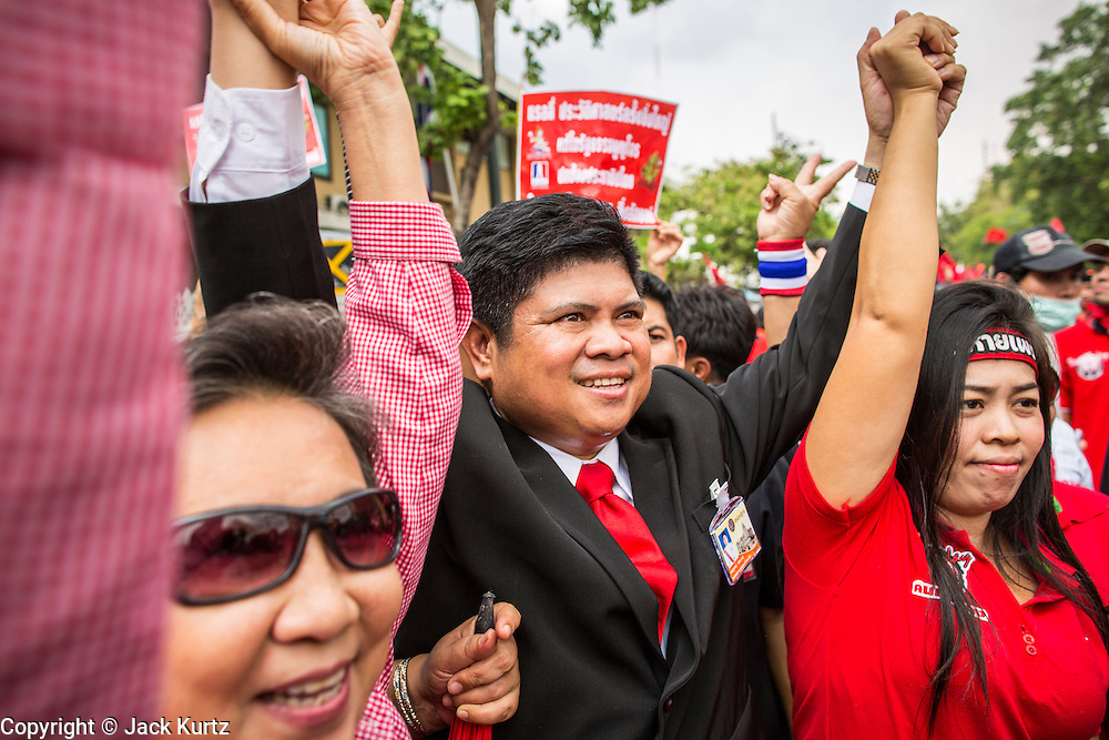 """10 DECEMBER 2012 - BANGKOK, THAILAND: Red Shirt leaders clasp hands in front the Thai Government House in Bangkok Monday. The Thai government announced on Monday, which is Constitution Day in Thailand, that will speed up its campaign to write a new charter. December 10 marks passage of the first permanent constitution in 1932 and Thailand's transition from an absolute monarchy to a constitutional monarchy. Several thousand """"Red Shirts,"""" supporters of ousted and exiled Prime Minister Thaksin Shinawatra, motorcaded through the city, stopping at government offices and the offices of the Pheu Thai ruling party to present demands for a new charter.         PHOTO BY JACK KURTZ"""