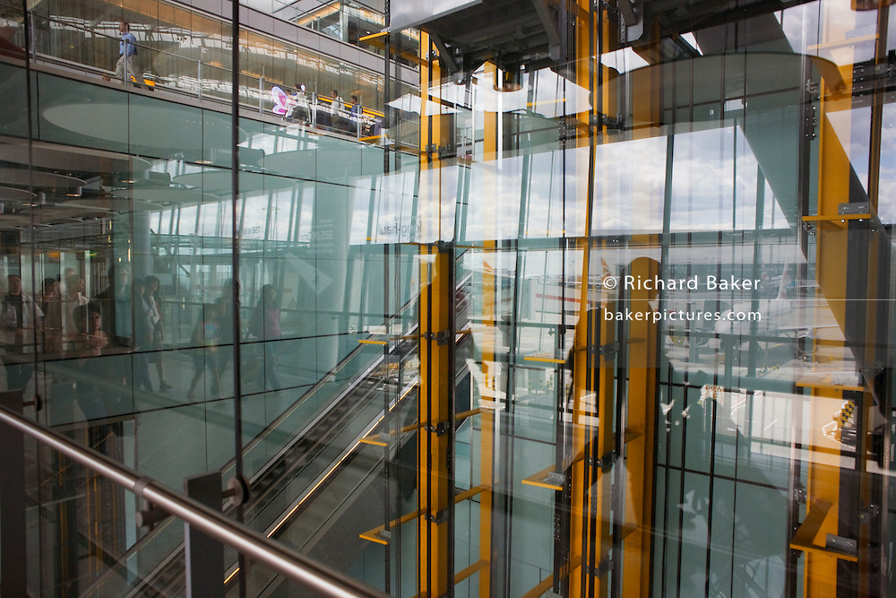Arriving passengers and reflected airport architecture at Heathrow's Terminal 5.