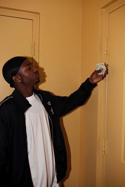 """Michael """"Lil' Mike"""" Miller"""" shows off a roll of bills at the _____ hotel during a bachelor party for a friend in Greenwood, Mississippi on February 18, 2011."""