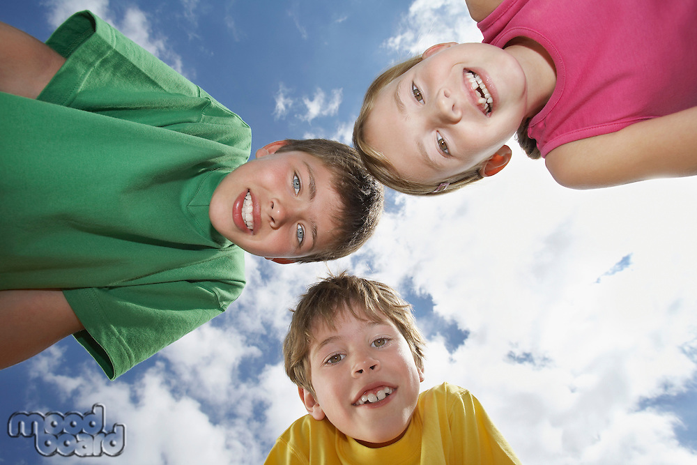 Portrait of two boys and girl (6-11) bending down view from below