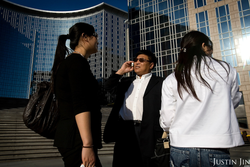 A businessman and his companions talk in front of the Grand Hyatt Hotel in Beijing, which is getting ready to host the 2008 Olympics.