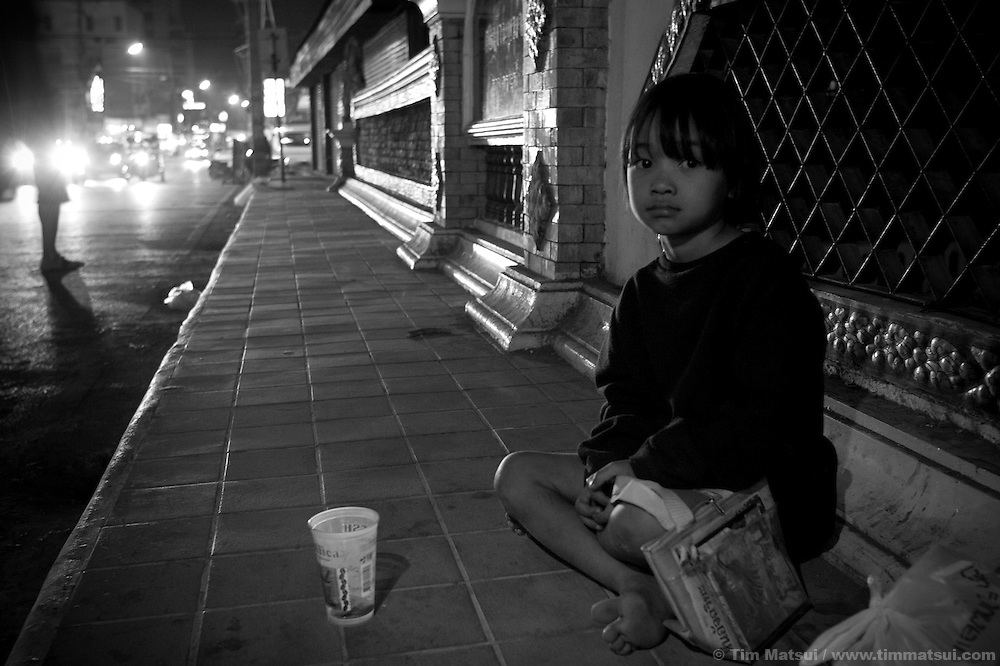 A young girl begging late at night on the streets of Chiang Mai in the red light district; her mother, with baby, is across the street also begging..Members of the Volunteer for Children's Development Foundation (VGCD) work the streets near the sex worker bars, talking with young prostitutes and street children about the opportunities their organization offer such as counseling, life skills training, emergency assistance, and temporary shelter. Many of VGCD's volunteers have been or still are sex workers who, while working, will watch for sexual and commercial exploitation of minors. According to VGCD members, children are often sent to beg or sell flowers to tourists in the bars; exposure to a highly sexualize atmosphere until the early hours of the morning puts the children at risk for exploitation and many wind up working in the sex industry either as juveniles or later as adults..