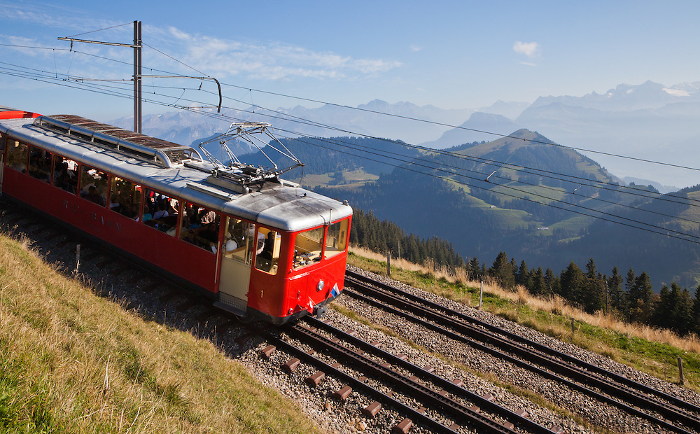 """A tourist train called the """"Rigibahn"""" taking tourists down from sightseeing on Mount Rigi in the Swiss Alps."""