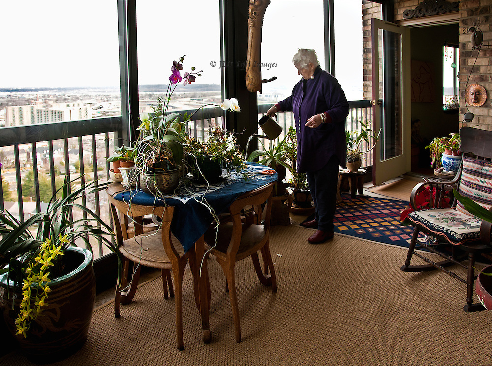 Middle aged woman with white hair watering her orchids on a glassed in balcony of an upscale luxury apartment in Alexandria, Virginia.