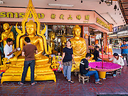 01 FEBRUARY 2017 - BANGKOK, THAILAND: Men work on a large statue of the Buddha while women make large traditional parasols at a shop that makes and sells Buddhist paraphernalia in Bangkok. The umbrellas are used as parasols to keep the sun off important Buddha statues and at formal events. In Thai culture, the parasols were used to provide shade for members of the royal family or representatives of the royal family.     PHOTO BY JACK KURTZ