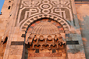 Courtyard entrance of the Isa Bey Mosque, built 1374-5, Selcuk, near Ephesus, Izmir, Turkey. The mosque was built in Seljuk style under the Emir of Aydin in honour of the Aydinid Isa Bey. Here we see the courtyard entrance with a honeycomb niche under the arch, with the brick minaret above. Columns and stones from the ruins of the nearby Greek and Roman city of Ephesus and the Temple of Artemis were incorporated into the building. The mosque was restored in 1934. Picture by Manuel Cohen