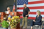 East Meadow, New York, U.S. September 10, 2020. SUSAN HUTCHINS, at far left podium, holds up photo of her son Kevin Colbert, who died after a plane hit South Tower on September 11, 2001. Nassau County Executive LAURA CURRAN sits at far right, as county commemorated 19th anniversary of September 11 terrorist attacks with Remembrance Ceremony at Eisenhower Park, with names read of 348 county residents killed that day. Event was held at Harry Chapin Lakeside Theater, instead of 9/11 Memorial across the pond, because of rain prediction.