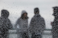 People standing on the outside deck on a Washington State Ferry in the rain seen through a window covered with raindrops, focus on raindrops.