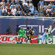 Bradley Wright-Phillips, New York Red Bulls, scores his sides first goal beating goalkeeper Josh Saunders, NYCFC, as David Villa, (right), NYCFC, looks on during the New York City FC Vs New York Red Bulls, MSL regular season football match at Yankee Stadium, The Bronx, New York,  USA. 28th June 2015. Photo Tim Clayton
