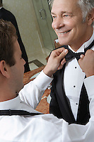 Young man tying middle-aged man's bow tie